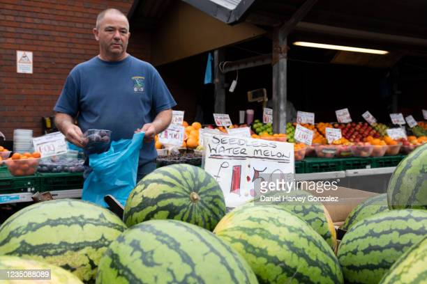 Market trader at an outdoor fresh fruit and vegetable stall bags a punnet of plums with rows of seedless watermelons in the foreground on 4th...
