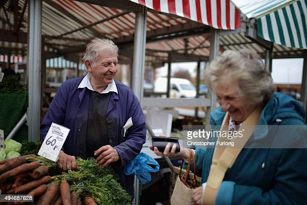 Market trader Brian Bradley shares a joke with a customer in Wolverhampton which has been declared the most miserable place in Britain on October 28...