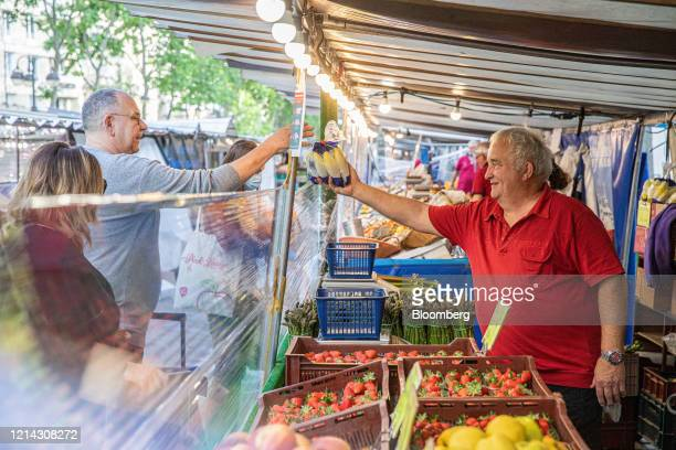 A market trader hands a customer a bunch of bananas over a protective cellophane screen on a fruit and vegetable stall at Marche SaxeBreteuil in...