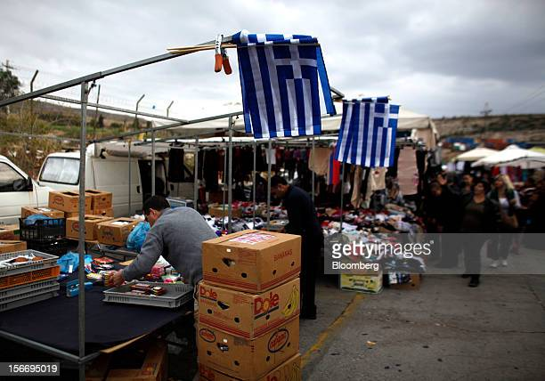 A market trader packs his goods away under Greek national flags flying from his stall at the at the 'Bazaar of Schisto' open market in Piraeus Greece...