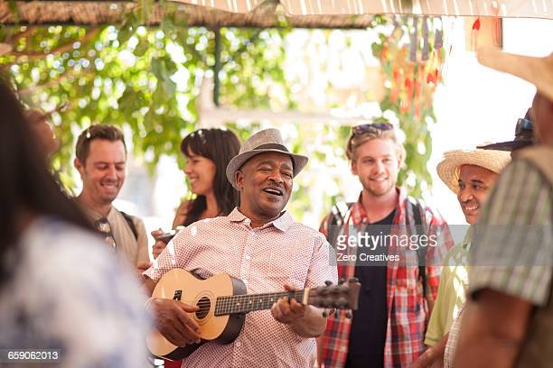 Market trader playing ukulele to entertain tourists