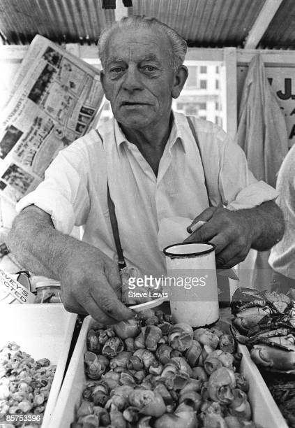 A market trader seeling jellied eels at a market place in the East End of London 1960s