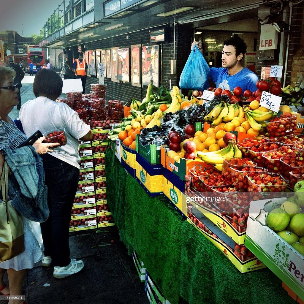 Market trader selling fruit, North London. : Stock Photo