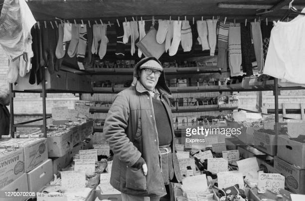 Market trader selling socks, tights and leg warmers in a street market, UK, 17th January 1985.