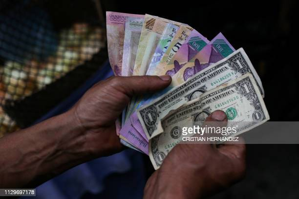 A market trader shows different currency notes in Caracas on March 10 during the third day of a massive power outage which has left Venezuelans...