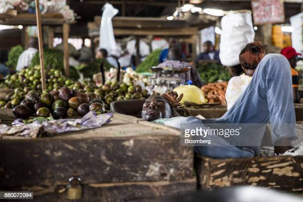 A market trader sleeps as he waits for customers in Mombasa Kenya on Thursday Nov 23 2017 The countrys Treasury has already cut this years growth...