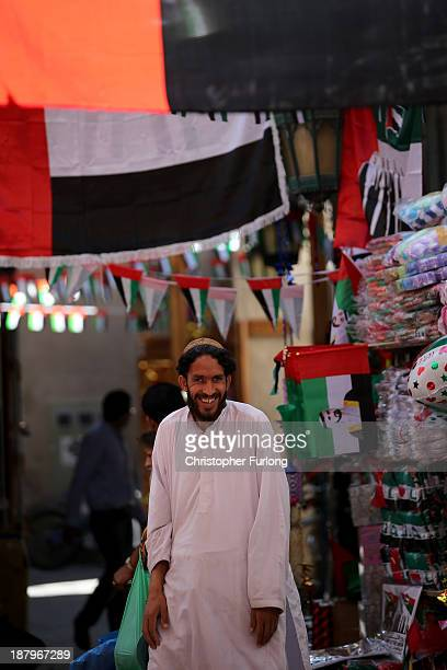 A market trader smiles as he sells flags and bunting to celebrate UAE National Day on November 13 2013 in Dubai United Arab Emirates Dubai is...