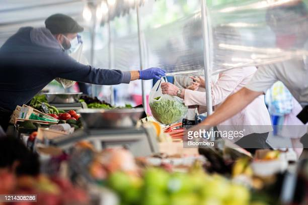 A market trader wearing a protective face mask hands a customer their purchase under a protective cellophane screen on a fruit and vegetable stall at...