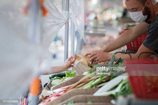 A market trader wearing a protective face mask hands a customer their fresh produce under a protective cellophane screen on a fruit and vegetable...