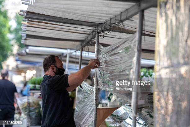 A market trader wearing a protective facial mask wraps cellophane around his fruit and vegetable stall while setting up for business at Marche...
