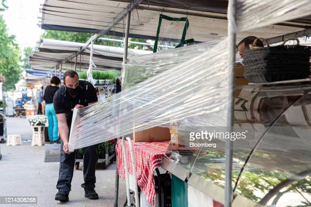 A market trader wearing a protective facial visor mask cellophane around his fruit and vegetable stall while setting up for business at Marche...