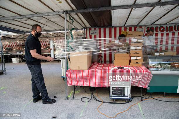 A market trader wearing a protective facial visor mask wraps cellophane around his fruit and vegetable stall while setting up for business at Marche...