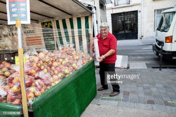 A market trader wearing a protective facial visor wraps cellophane around his fruit stall while setting up for business at Marche SaxeBreteuil in...