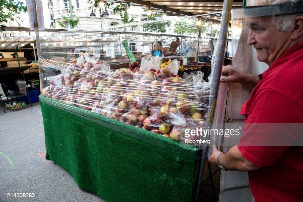 A market trader wearing a protective facial visor wraps plastic around his fruit stall while setting up for business at Marche SaxeBreteuil in Paris...