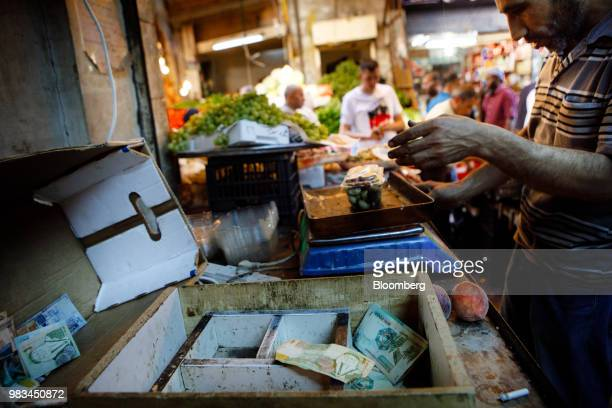 A market trader weighs plums beside a tray full of Jordanian dinar banknotes at a local fruit and vegetable market in Amman Jordan on Thursday June...