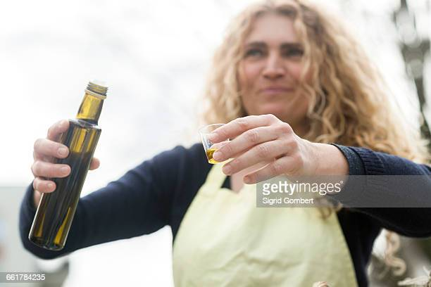 market trader with bottle of olive oil - sigrid gombert stock pictures, royalty-free photos & images