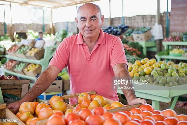 market trader with tomatoes - banca de mercado imagens e fotografias de stock