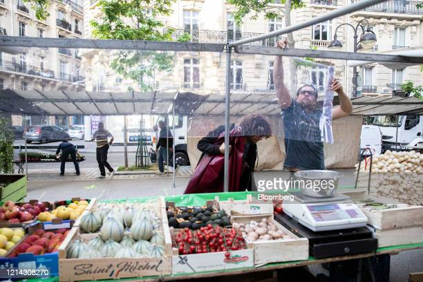 A market trader wraps cellophane around a fruit and vegetable stall while setting up for business at Marche SaxeBreteuil in Paris France on Thursday...