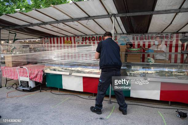 A market trader wraps cellophane around his fruit and vegetable stall while setting up for business at Marche SaxeBreteuil in Paris France on...