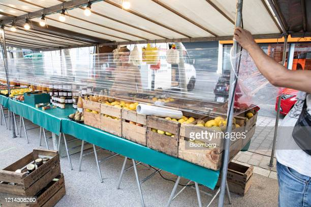 A market trader wraps cellophane around his fruit stall while setting up for business at Marche SaxeBreteuil in Paris France on Thursday May 21 2020...