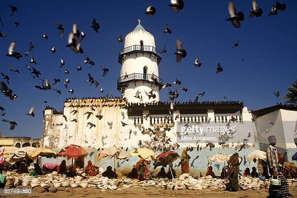 Market traders sit beneath the The Hamoudi Mosque while a flock of birds eye up the food on sale below Djibouti City