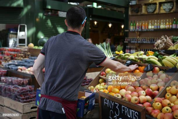 A market tredr picks up an orange as he works on his stall at Borough Market as it reopens to the public following the terrorist attack on June 14...