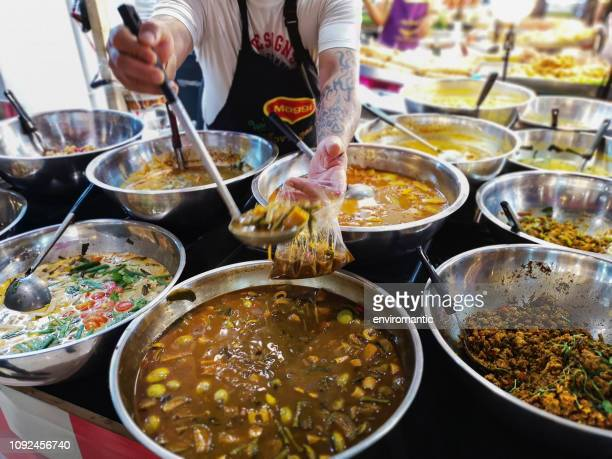 market vendor at a thai fastfood market scoops a portion of a thai curry soup into a plastic bag for a customer's order. - curry soup stock photos and pictures