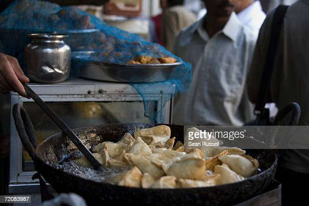 market vendor cooking samosa - samosa stock photos and pictures