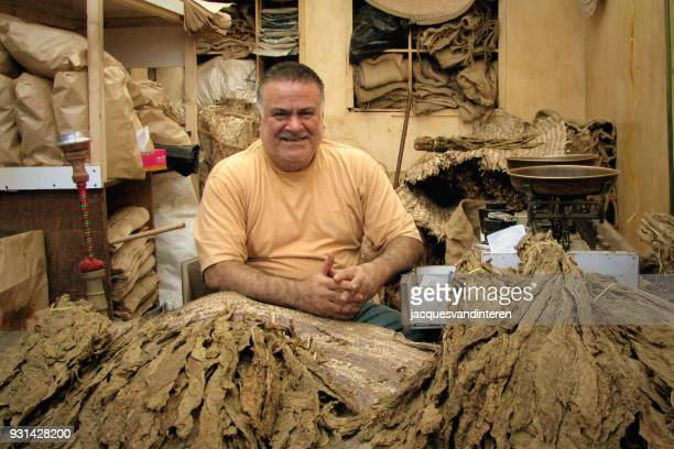 market vendor in bahrain, selling tobacco leaves - manama stock pictures, royalty-free photos & images