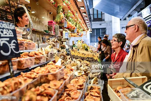Market Vendor selling mushrooms talking to customers
