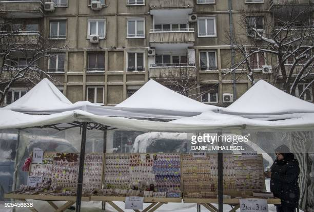 Market vendors sell traditional spring charms martisor under makeshift shelters in central Bucharest on February 28 2018 Romanians will be marking...