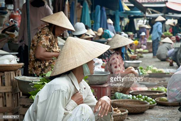 market vendors wearing traditional conical hats in hoi an, vietnam - asian style conical hat stock pictures, royalty-free photos & images