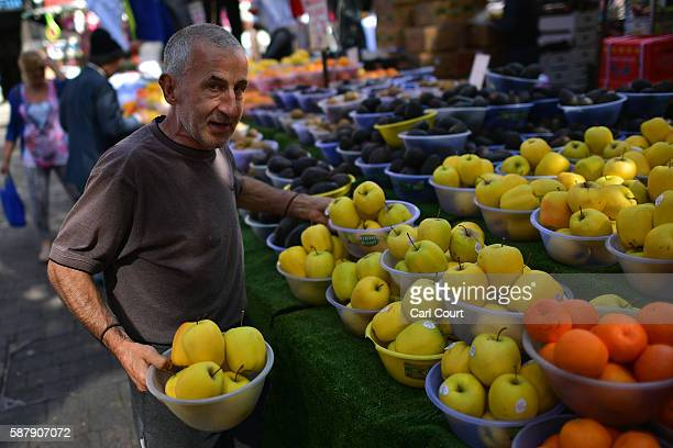 A market worker carries bowls of apples for display on a fruit and vegetable stall in Walthamstow market on August 9 2016 in London England...