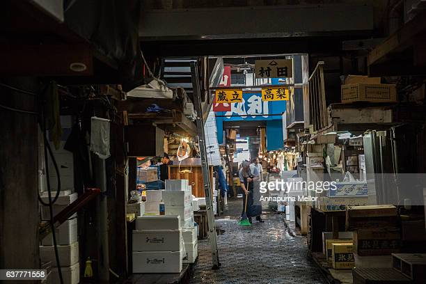 A market worker sweeps the floor at the Tsukiji Fish Market in Tokyo, Japan