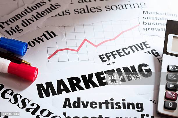 Marketing headlines with calculator, pens and sales graph