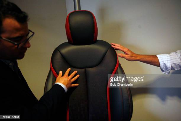Marketing vice president David Giddings left and David O'Connell inspect a finished leather seat cover at Katzkin Leather which produces leather...