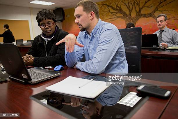 Marketplace guide Chris Casazza, right, helps resident Johanne Jean Louis sign up for a health insurance plan under the Affordable Care Act at an...