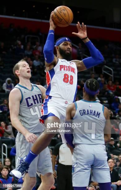 Markieff Morris of the Detroit Pistons passes the ball against defenders Devonte' Graham and Cody Zeller of the Charlotte Hornets during the second...