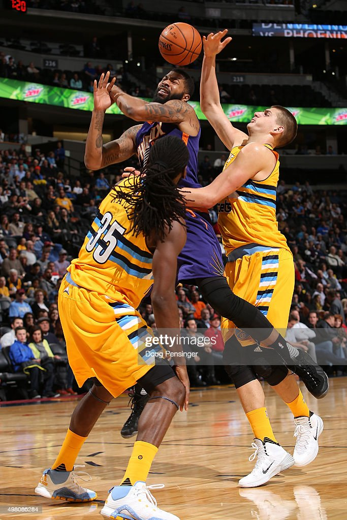 Markieff Morris #11 of the Phoenix Suns is fouled by Nikola Jokic #15 of the Denver Nuggets as Kenneth Faried #35 of the Denver Nuggets follows the play at Pepsi Center on November 20, 2015 in Denver, Colorado.