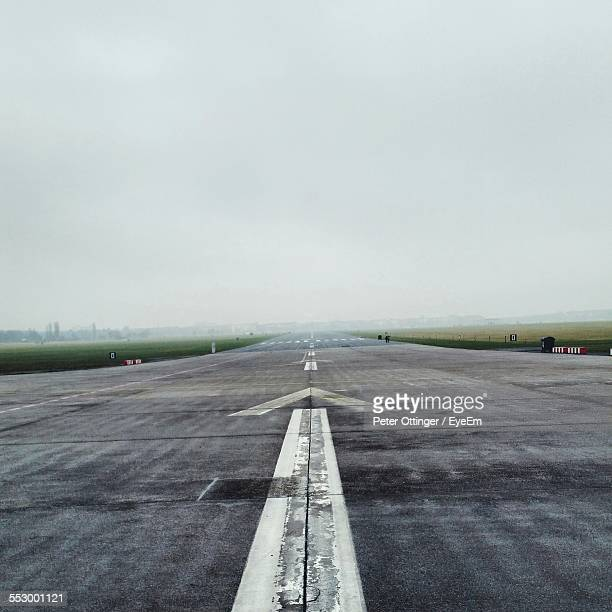 Markings On Airport Runway Against Clear Sky
