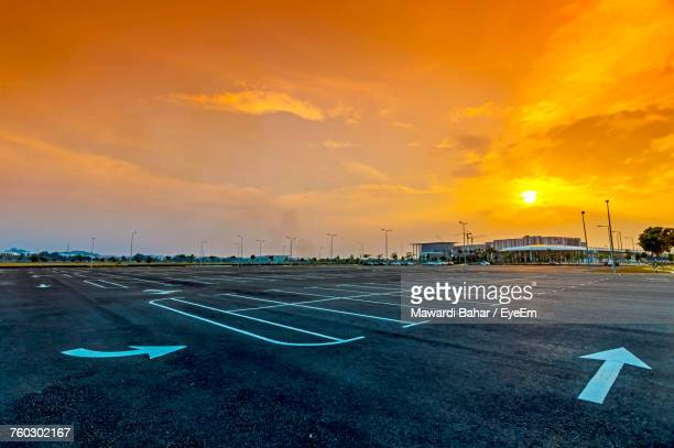 Markings On Empty Parking Lot Against Sky During Sunset
