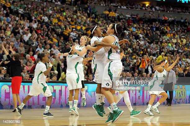 Markisha Wright and Kayla McBride of the Notre Dame Fighting Irish celebrate along with their teammates after they won 8375 in overtime against the...