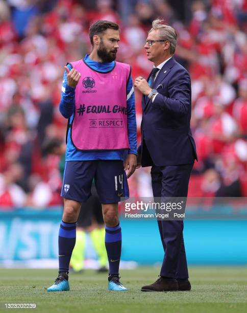 Markku Kanerva, Head Coach of Finland speaks with Tim Sparv of Finland prior to the UEFA Euro 2020 Championship Group B match between Denmark and...
