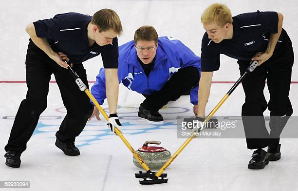 Markku Uusipaavalniemi of Finland releases the stone as Kalle Kiiskinen and Teemu Salo of Finland brush the ice during the Gold medal match of the...
