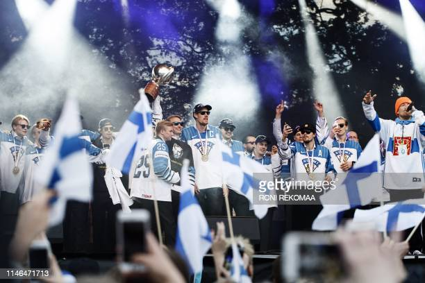 Marko Anttila captain of the Finnish ice hockey gold medal team and team mates cheer the crowd of hockey fans who gathered to celebrate in Helsinki...