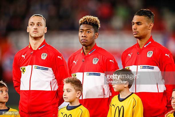 Marko Arnautovic David Alaba and Rubin Okotie of Austria line up during the national anthem prior to the international friendly match between Austria...
