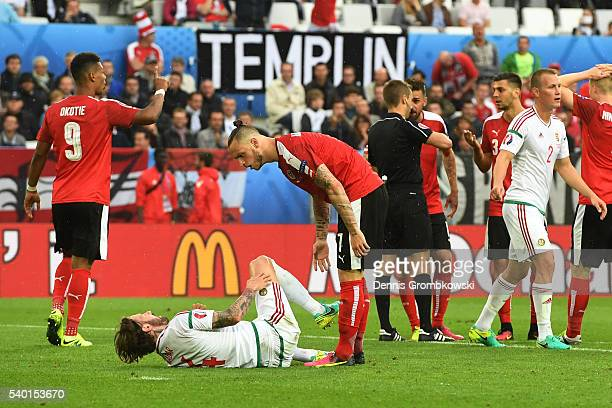 Marko Arnautovic of Austria argues with Tamas Kadar of Hungary while Aleksandar Dragovic of Austria is shown a red card by referee Clement Turpin...