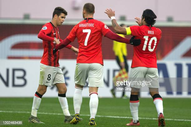 Marko Arnautovic of Shanghai SIPG celebrates for scoring a goal with teammate Hulk and Oscar during the AFC Champions League Preliminary Round match...