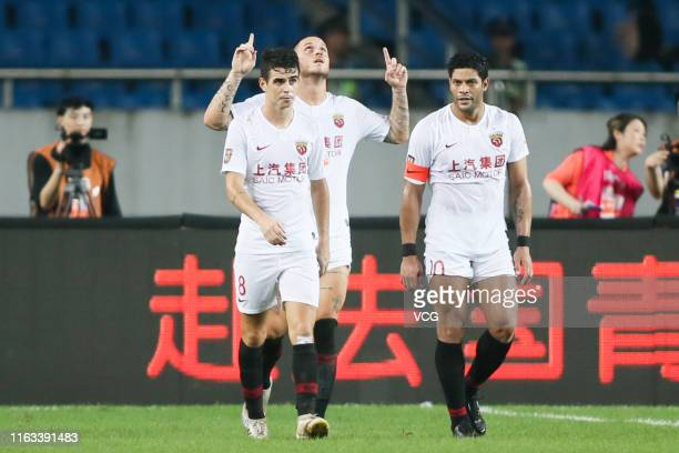Marko Arnautovic of Shanghai SIPG celebrates with team mates Oscar and Hulk after scoring a goal during the 19th round match of 2019 Chinese Football...