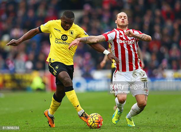 Marko Arnautovic of Stoke City and Jores Okore of Aston Villa compete for the ball during the Barclays Premier League match between Stoke City and...